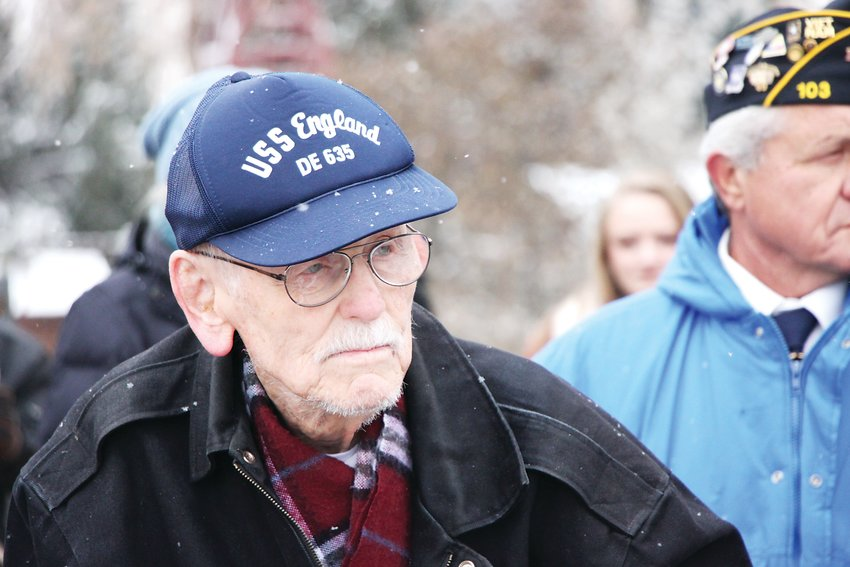 "Charles Goodwin stands as a choir performs ""Anchors Aweigh,"" the march song of the United States Navy. Goodwin, 96, was the sole World War II veteran in attendance at the ceremony."
