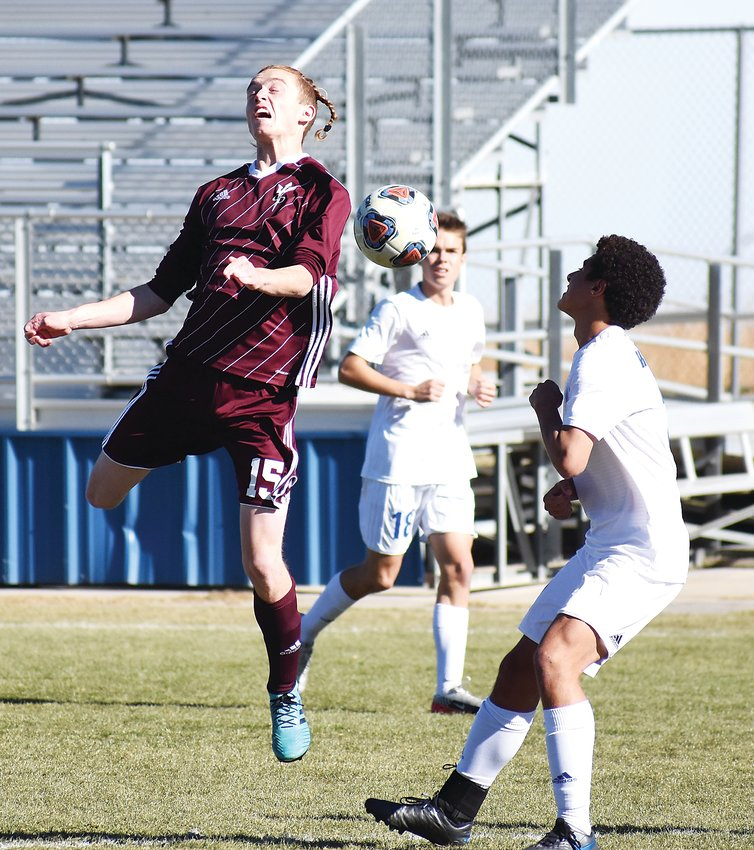 Golden senior Zach Chapman (15) attempts to direct a header on goal during the Class 4A state quarterfinal game Saturday at the North Area Athletic Complex.
