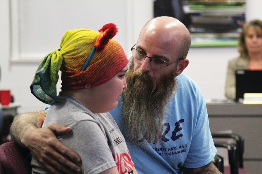 Marley Porter, 14, becomes emotional as her father, Mark, consoles her at the Nov. 12 Douglas County School Board meeting.