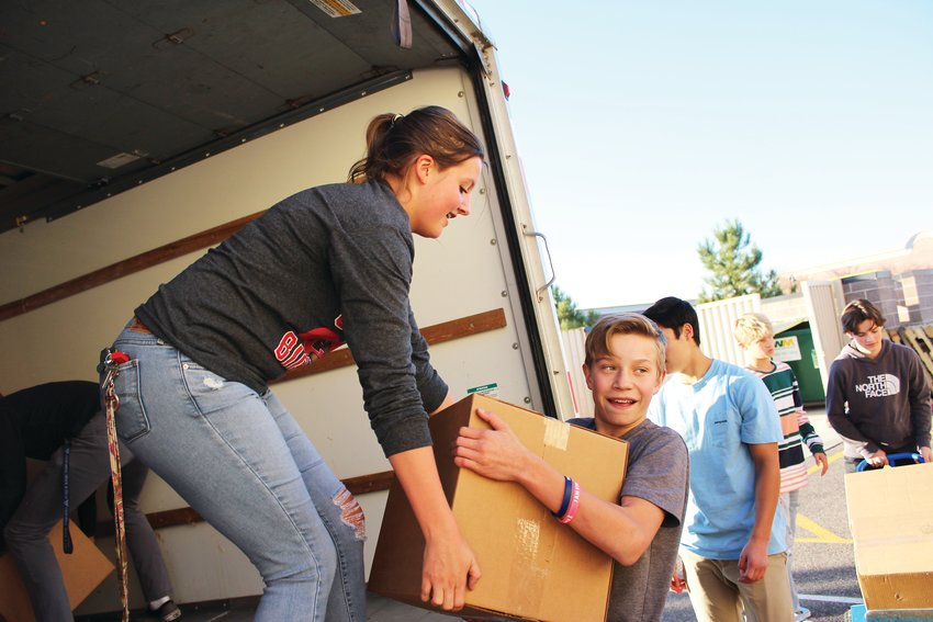 "Megan Arnett, Chaparral student body president, hands a box off to Tanner Westenskow Nov. 13 at the Parker Task Force. Chaparral holds a food drive during ""Wish Week"" every year to donate to the Parker Task Force."