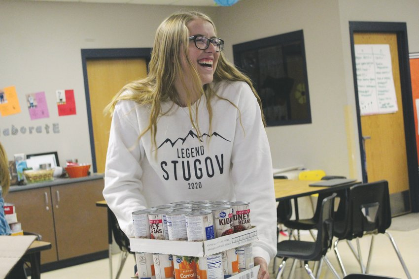 Ally Lowe carries cartons of canned food to the student government classroom at Legend High School Nov. 15.