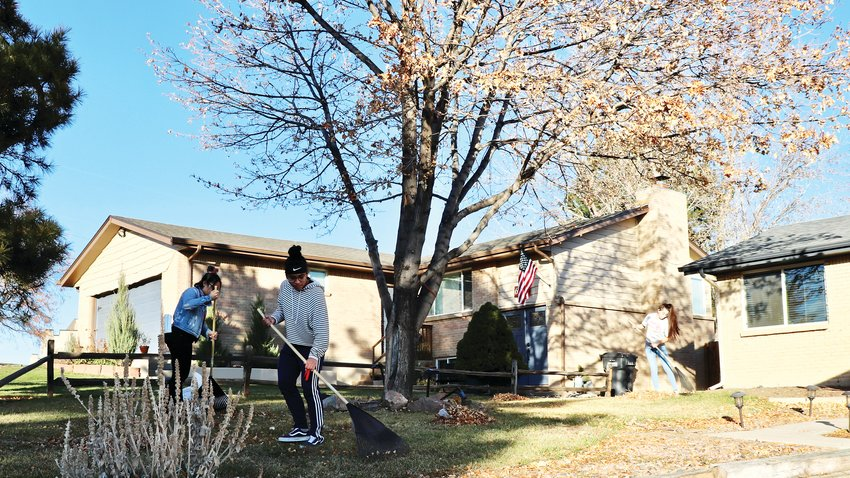 "Students Rayanne Gronquist, left, Nicole Poot and Mada Casados, who are part of the athletic leadership team at Arvada High School, rake leaves in a nearly neighborhood. ""It's important because it gets a good face for our student body out there, and it helps us to bond and give back to others,"" Gronquist said."
