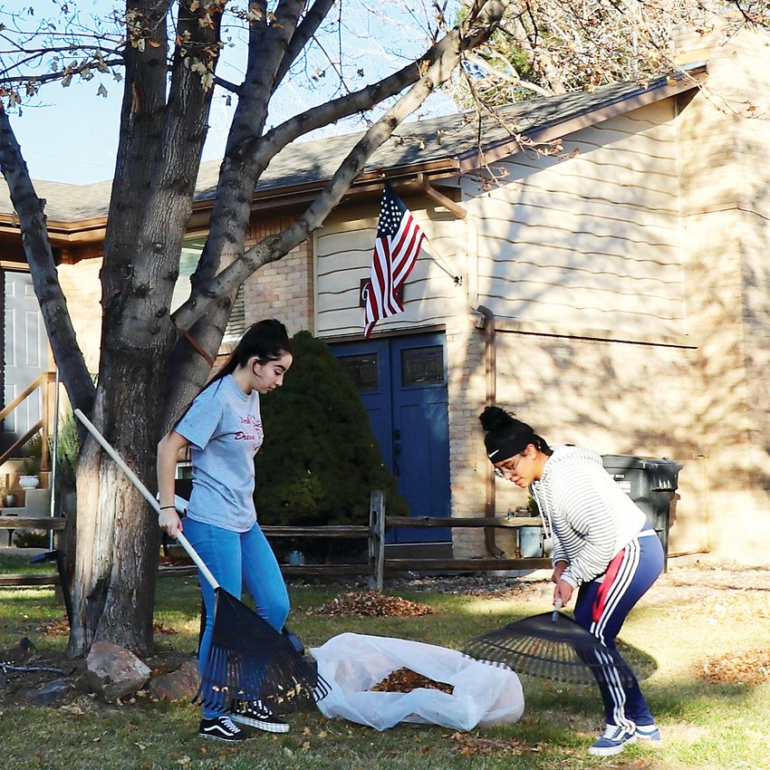 Mada Casados and Nicole Poot collaborate to move piles of leaves out of a neighbor's yard. The team typically works in the neighborhoods surrounding Arvada High School.
