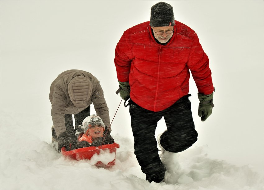 Grandpa Pete Schuster, of Sturgeon Bay, Wisconsin, and mom Michelle Schuster of Westminster combine efforts to get Latham Schuster, 4, up the sledding hill at Westminster's Cotton Creek Park during Nov. 26 snow storm. Grandpa and Grandma are in Colorado for Thanksgiving and the family decided to take advantage of the holiday storm. The family braved blowing snow and were the only riders at the sledding hill that morning.