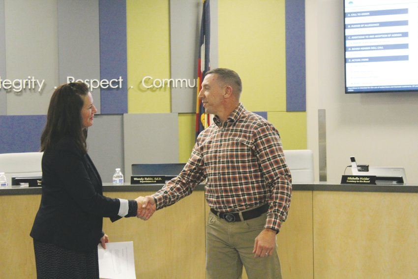 Tena Prange, secretary for the Englewood Schools Board of Education, shakes hands with the newest member of the board, Steven Leflar. He is joining Gary Manfre in replacing former board members Kevin Ebert and Sharon Scheminske.