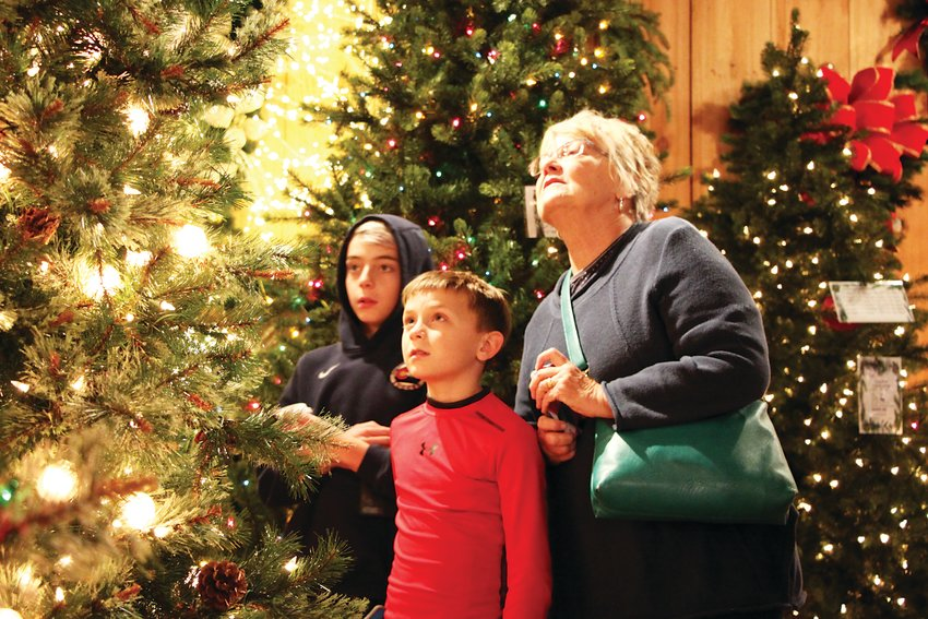 Eleven-year-old Anders Larock, left, his brother Ethan and their grandma Vicki Larock-Lieb shop for Christmas trees at St. Nicks in Littleton.