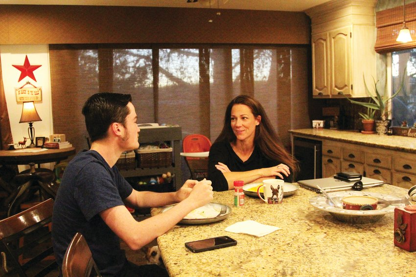 Ben Wann speaks with his mother, Amber, over breakfast on Nov. 18.