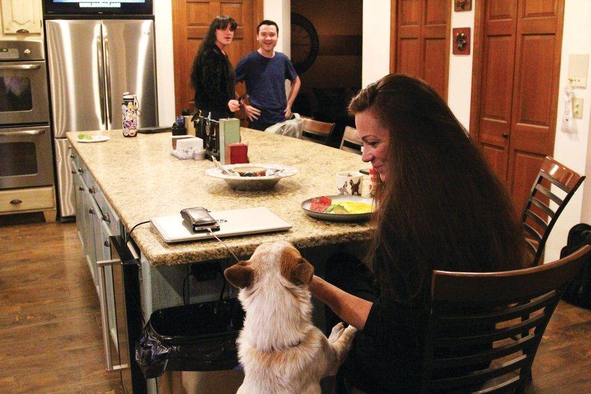 The family dog, Bindi, jumps up for a nibble from Amber Wann as she eats breakfast on Nov. 18.
