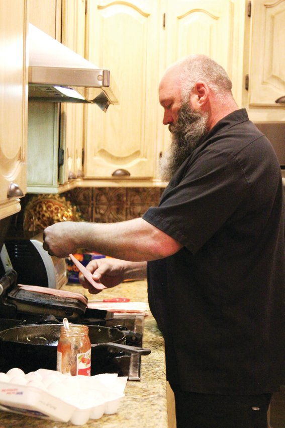 Brad Wann cooks up turkey, hashbrowns, omelettes and avocado slices for his family before his daughter and son leave for high school.