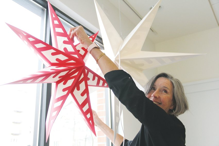 Stephanie Thomas, a member of the SoSu Art Collective, hangs decorations Nov. 27 for the group's holiday art sale in early December.
