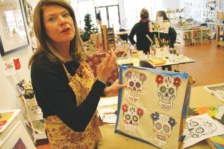 Janet Moore, a member of the South Suburban Artist Collective, discusses one of her pieces Nov. 27 at the group's studio at The Streets at SouthGlenn in Centennial.