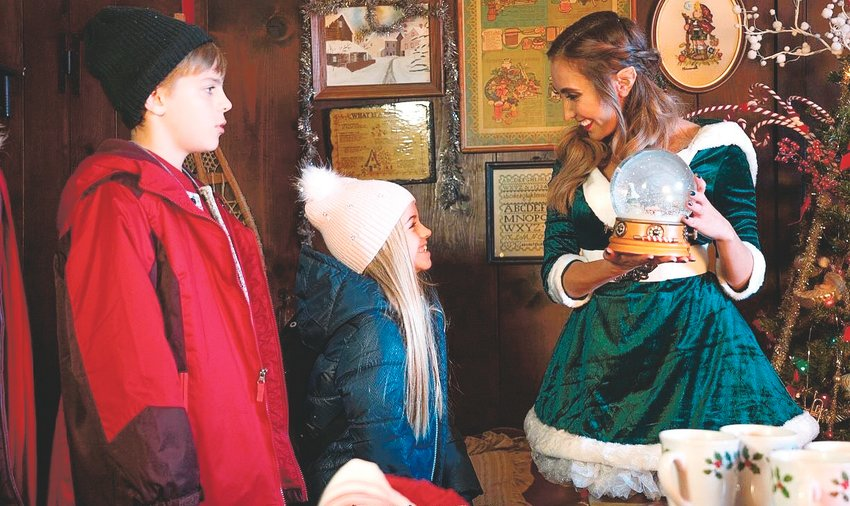 "Chelsea Vale, right, with the two actors playing the kids whose family needs saving in ""My Adventures with Santa"" on the ""Santa's House"" set."