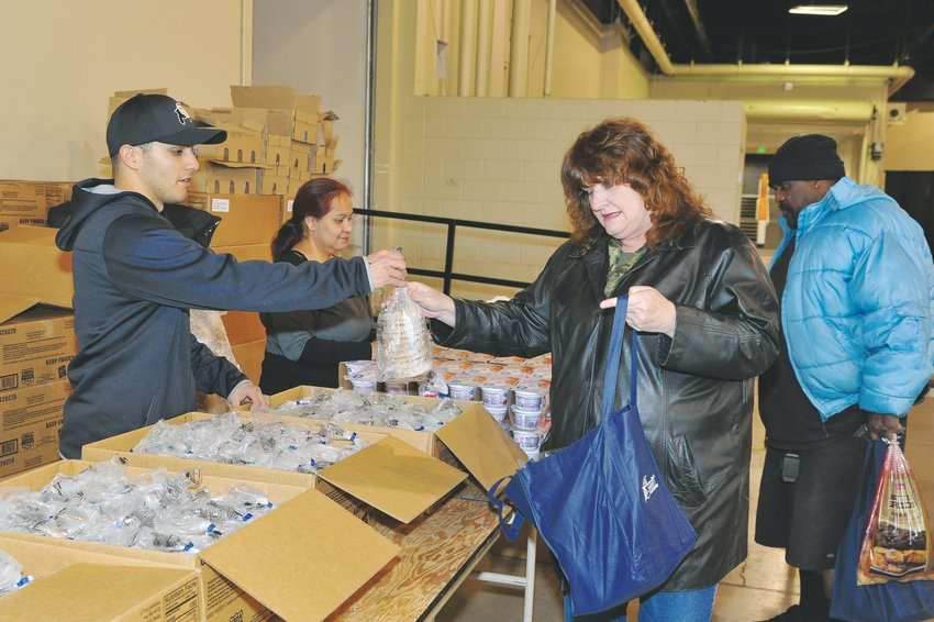 Renee Neal, of Denver, right, receives some meat patties from Abraham Rodriguez of Westminster, during the Adams County Sheriff's annual Operation Freebird November 23, at the Denver Merchandise Mart.
