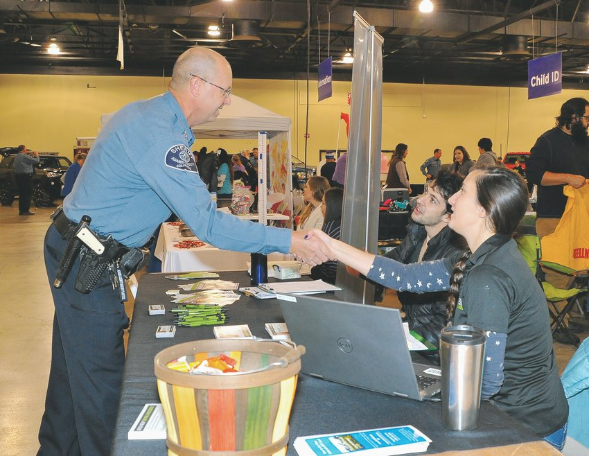 Adams County Sheriff Rick Reigenborn, left, greets Hunger Free Colorado representatives Machayla Fortin of Arvada and Jordan Lamport of Denver, during his department's annual Operation Freebird food giveaway, at the Denver Merchandise Mart Nov. 23.
