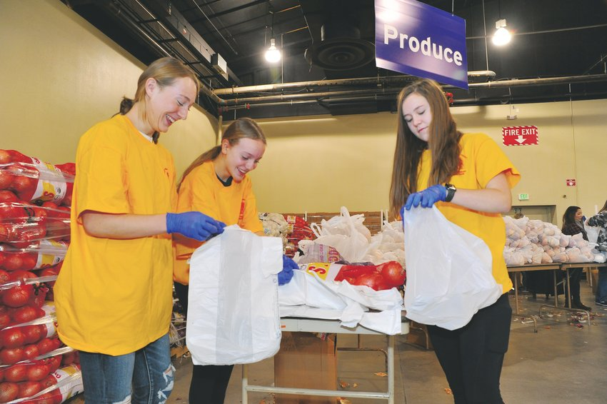 Lauryn Munsch, left, Lizzy Crawford, and Rachel Kaiser, all freshmen at Horizon High School, prepare onions for giveaway, during 2019's Adams County Sheriff Department's Operation Freebird November 23, at the Denver Merchandise Mart. The 14-year-olds from Thornton participate in Horizon's SOAR honors program.