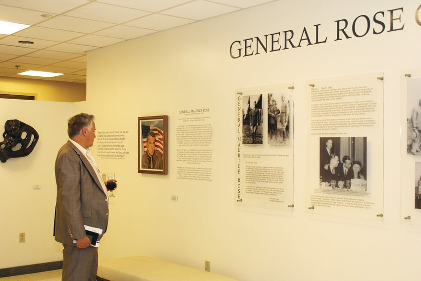 A guest reads about photographs in the new museum space at Rose Medical Center. The museum was added for the anniversary of the hospital and includes the cornerstone dedicated by then Gen. Dwight D. Eisenhower in 1948.
