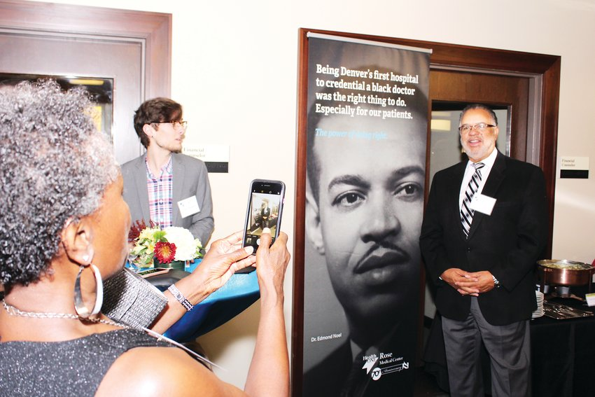 Regina Jackson takes a photo of her husband, the Hon. Gary Jackson next to a banner of Dr. Edmond Noel. Gary Jackson said that Noel was his family doctor as a child.