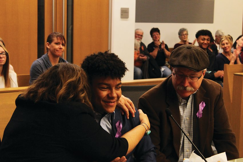 Morgan Richards, left, hugs Jassir, 14, during the court proceedings to finalize his adoption, with Jeff Richards. The Richardses first matched with Jassir for adoption several years ago, but he first moved in the summer of 2018.