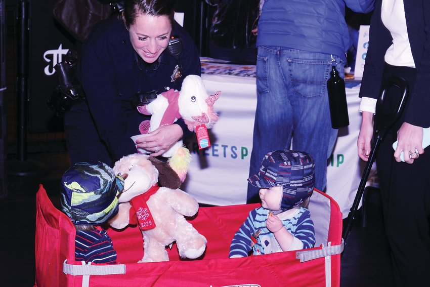 Denver Police Officer Teresa Gillian hands out stuffed animals to Aiden, left, and Wes Kuechenmeister. Gillian is the community liaison officer for District 6 of the police department.