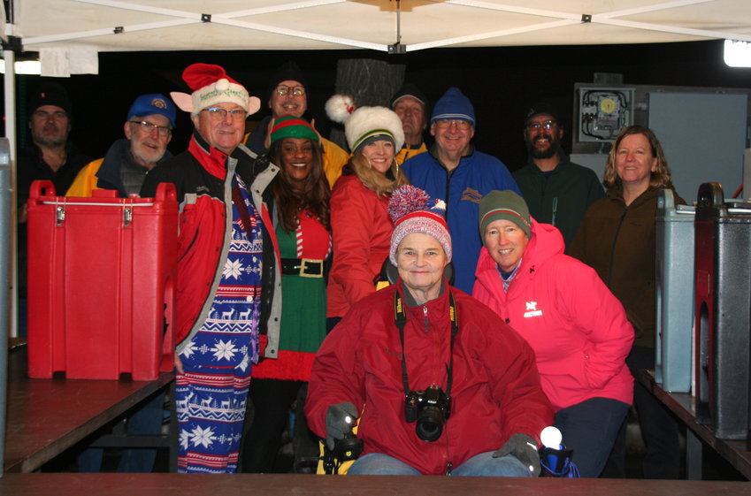 The Golden Lions Club gathers for a photo at the club's free hot cider stand during the Candlelight Walk on Dec. 6.