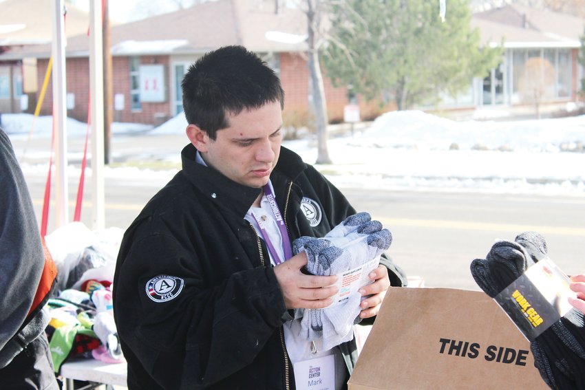 Mark Burroughs holds a pair of socks at The Action Center human-services nonprofit in Lakewood. The Action Center sought out to collect 10,587 pairs of new socks in honor of the 10,587 people in Colorado who are homeless.