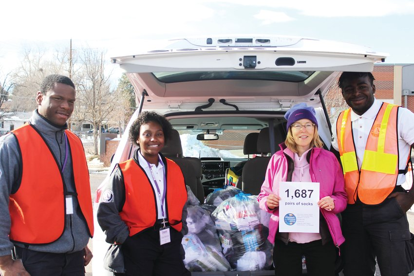 Juvens Jean-Noel, left, Shea Narive, Lee Ann Hufford and Shaun Thomas stand in front of a vehicle that was carrying 1,687 pairs of socks. The socks were collected by the Concordia Lutheran Church in Lakewood.