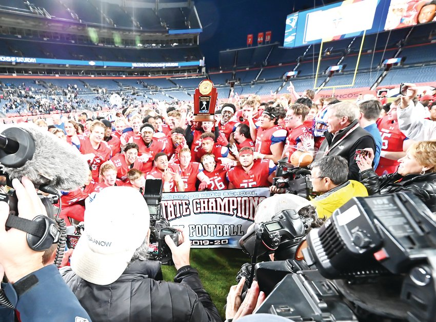 The Cherry Creek football team raises the championship trophy and banner after defeating Columbine 35-10 on Dec. 7 at Empower Field at Mile High.