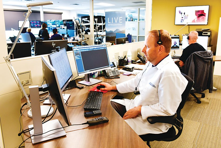 Dr. Mike Mitchell, an emergency medicine physician, sits at the UCHealth Virtual Health Center in Aurora. The center connects patients to a variety of virtual services including video appointments, virtual sitting and vital monitoring.