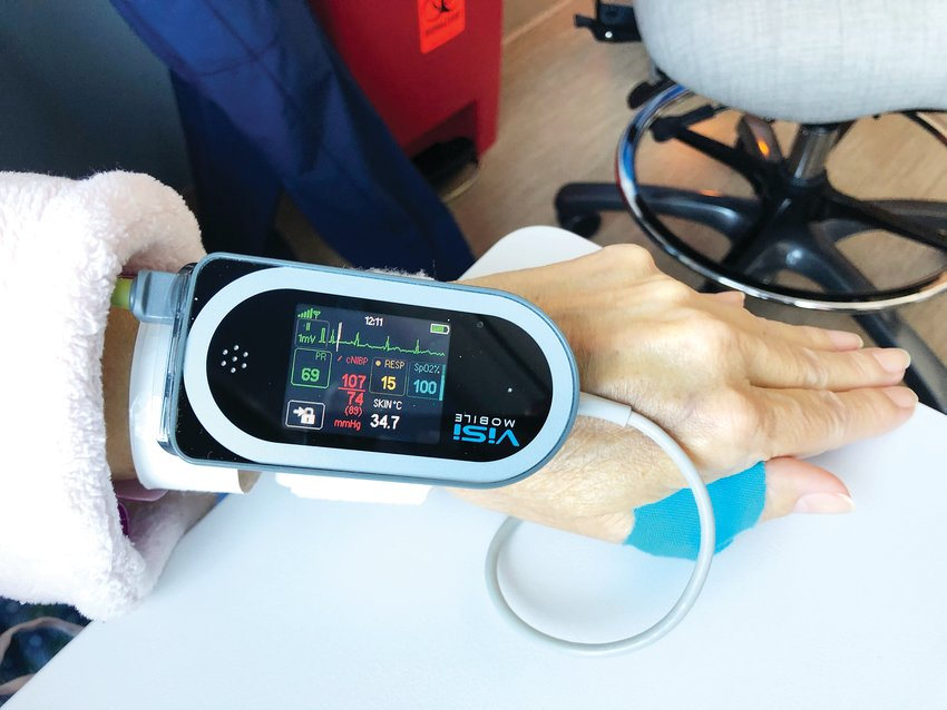 A vital-monitoring machine attached to Kathryn McCune, 63, shows her blood pressure, heart rate, respiratory rate, oxygen saturation and skin temperature.