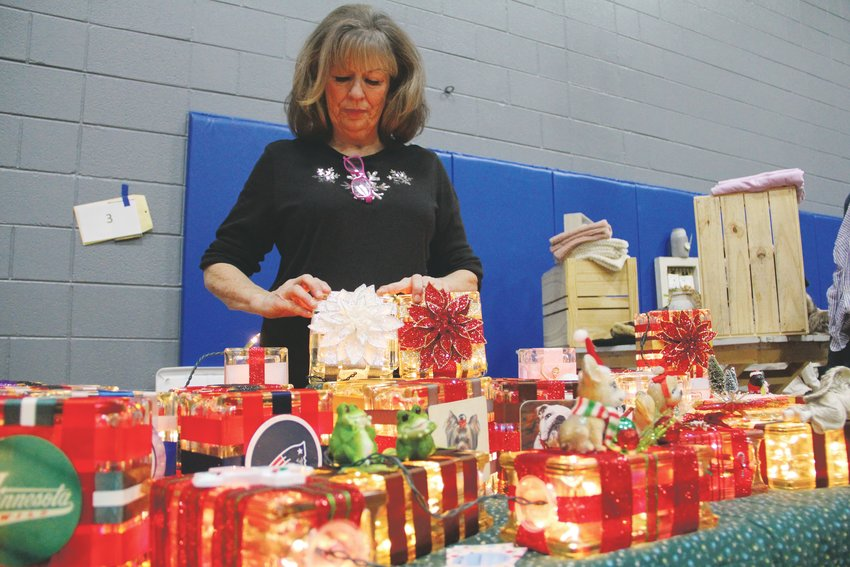 Highlands Ranch resident Mona Leonida, 70, stands over her holiday crafts — glass blocks bearing the logos of sports teams, with string lights inside — Dec. 7 at Goodson rec center.