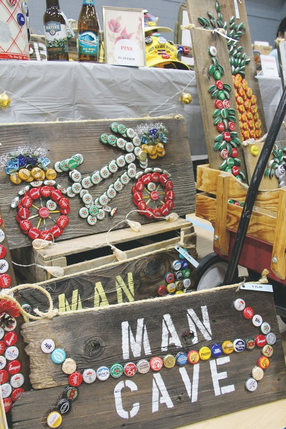 "Art made of beer bottle caps and reclaimed wood — one piece bearing the phrase ""man cave"" — sits Dec. 7 at Goodson Recreation Center's annual craft fair."