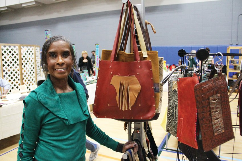 "Anita Cooper, 68, stands next to leather accessories she sells Dec. 7 at Goodson Rec Center. Her business name is ""Nita Louise."""