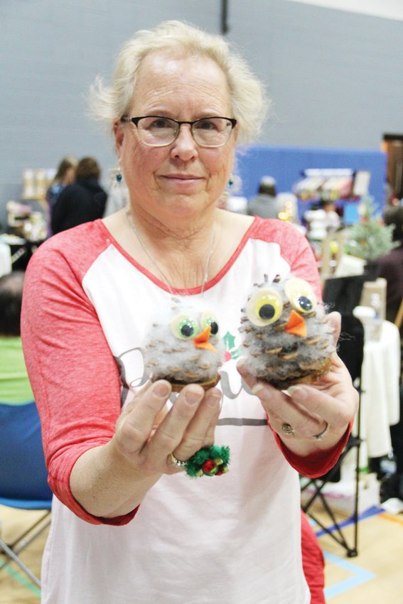 Christie Mclagan, 61, holds up owls made with pinecones at a South Suburban Parks and Recreation craft fair.
