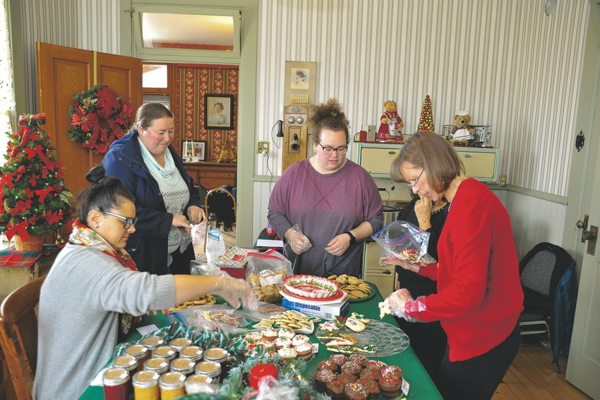 Northglenn volunteers from left, Lauren Weatherly, Elizabeth Candelario, Sara Dusenberry, and Diane Cooksey, arrange baked goods for sale at 2019 Old Fashioned Christmas, on Saturday, Dec. 7, at the Stonehocker Farm homestead, 10950 Fox Run Parkway.