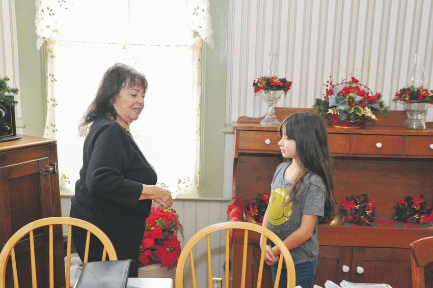 Northglenn City Councilor Joyce Downing, left, directs her great-granddaughter, Dolly Carter, 8, as they prepare for the city's annual Old Fashioned Christmas open house at the Stonehocker homestead Dec. 7.