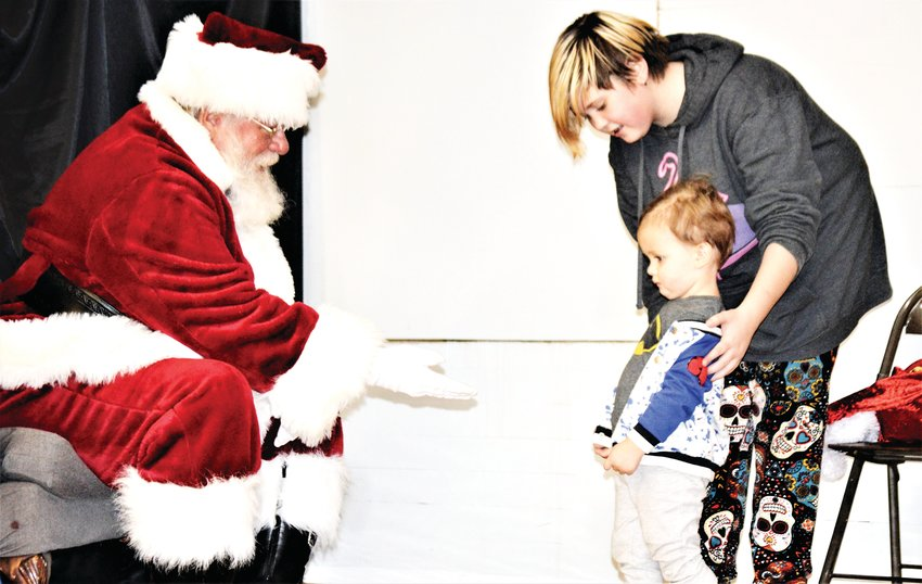 Bradley Ivarson of Arvada, 2, doesn't seem so sure about visiting with Santa Claus while sister Victoria Losievsky, 11, offers a bit of encouragement Dec. 5 in the Westminster Grange Hall, part of the Westminster Historical Society's Hometown Christmas celebration.