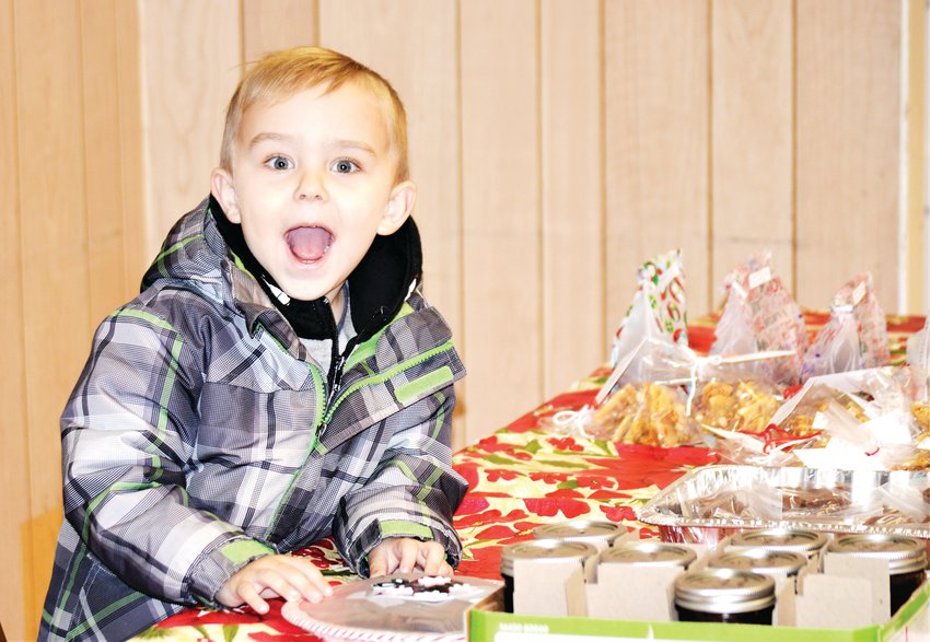 Maverick Sloan, of Westminster, mugs while working behind the candy and Christmas treats table inside the Westminster Grange Hall Dec. 5. The hall was open for the Westminster Historical Society's Hometown Christmas celebration.