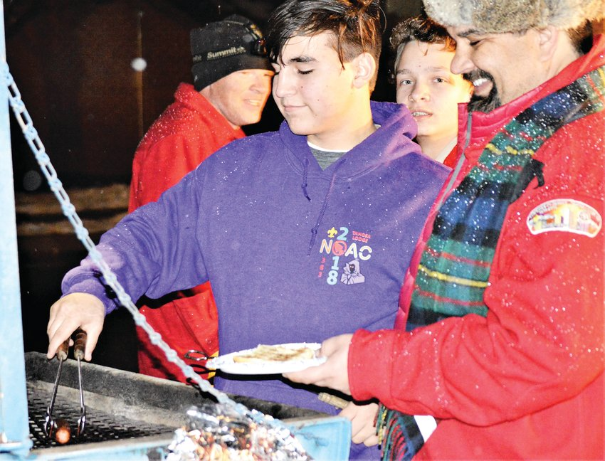 Scout Paul Alvarez of Northglenn Troop 311 prepares a hot dog on a grill set up outside of Westminster's Fire Station 1 Dec. 5, part of the Westminster Historical Society's Hometown Christmas celebration. Father Louis Alvarez waits to be served.