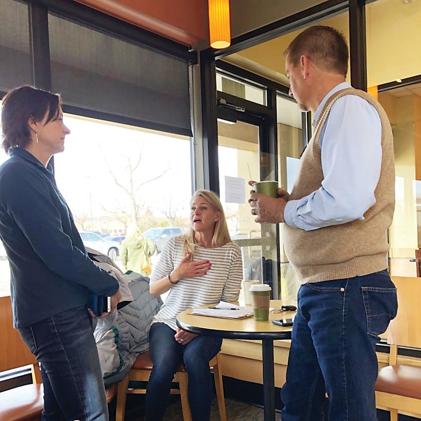 At the monthly Jeffco Public Schools Coffee Talk Dec. 4, parents Joan Wagner, left, and Amanda Dodek discuss differences between district neighborhood schools and district charter schools with school board member Brad Rupert.
