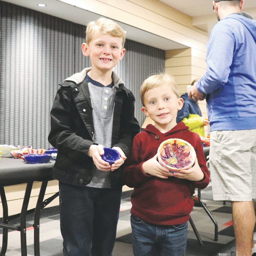 "Foster Elementary students Olin and Vic Jacobson purchase the ceramic bowls they previously made for the event. ""We really wanted to get our bowls after we made them,"" Olin said."