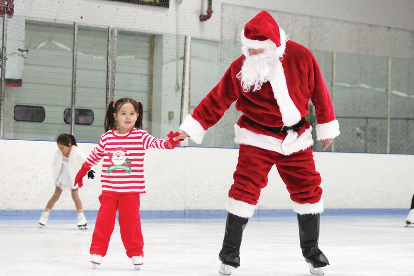 Santa Claus helps a little skater across the rink at the South Suburban Ice Arena on Dec. 13.