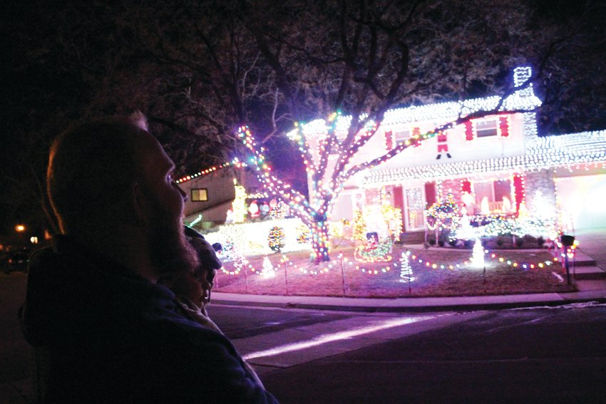 David Martin admires his handiwork carrying his newborn son, Matthew. Martin said he stands there, across the street from his house, to enjoy the full view of his house covered in more than 20,000 light bulbs.