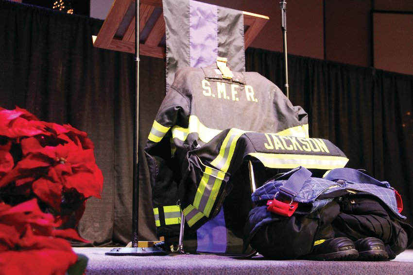 The uniform of former South Metro Fire Rescue Assistant Chief Troy Jackson sits at the foot of the stage at Denver First Church, in front of the lectern for speakers.