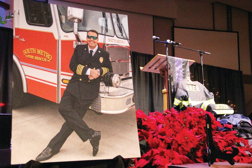A large photo of former South Metro Fire Rescue Assistant Chief Troy Jackson sits at the foot of the stage at Denver First Church. Jackson's uniform lay near it, at right.