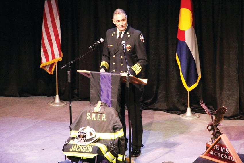 South Metro Fire Rescue Chief Bob Baker speaks Dec. 20 at the memorial service for former Assistant Chief Troy Jackson. At the foot of the stage, Jackson's uniform lay.