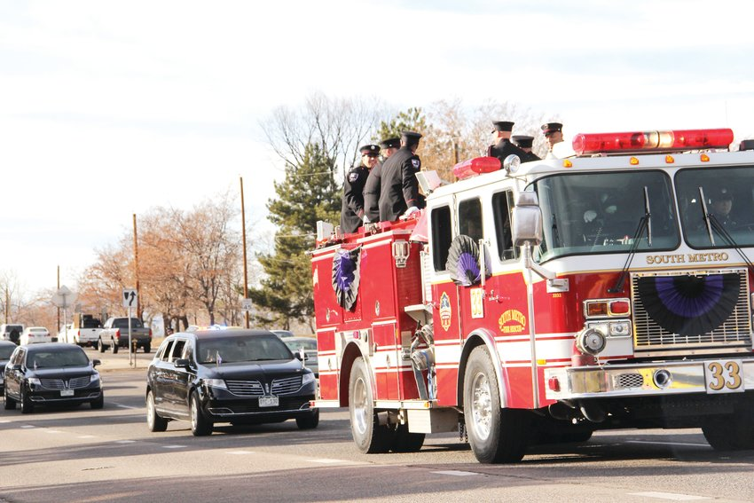 Fire rescue personnel ride atop a truck on East Hampden Avenue near South Colorado Boulevard in the procession of emergency vehicles after the memorial service for Troy Jackson Dec. 20.