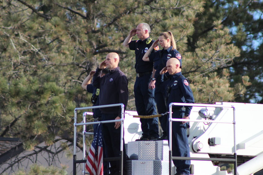 Fire fighters from the Castle Rock Fire Department stand atop a firetruck and salute as the procession for Troy Jackson drives through Centennial Dec. 20.