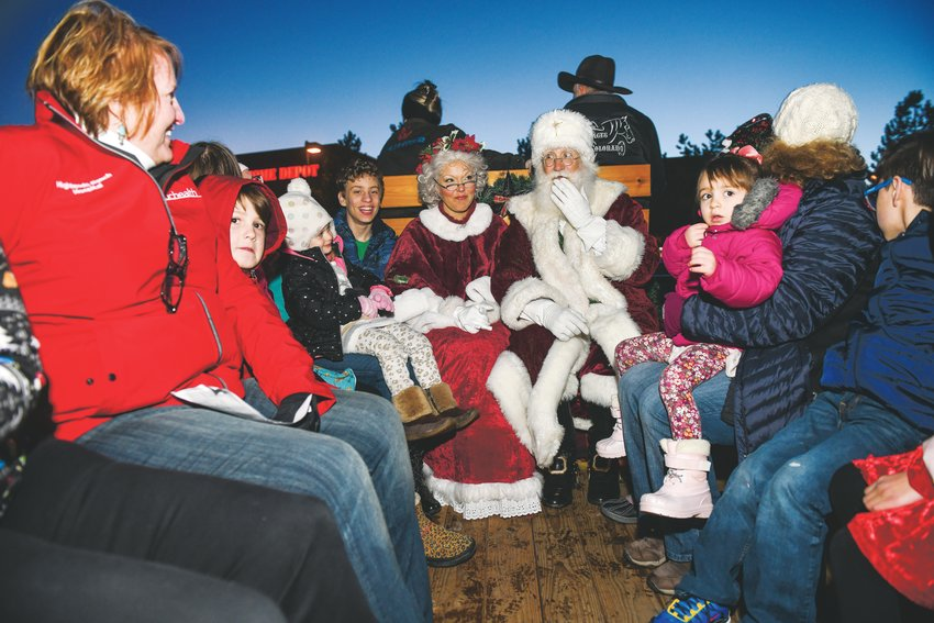 At left, Santa and Mrs. Claus sit with attendees of the Highlands Ranch Community Association's Hometown Holiday event Dec. 6. The event also featured vendor booths, caroling and food.