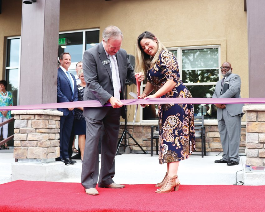 Mayor Marc Williams. and Janelle Markel — who has graduated from Hope House, gotten a job as a machinist and bought her own home — cut the ribbon at the grand opening of the Hope House Resource Center, 6475 Benton St.