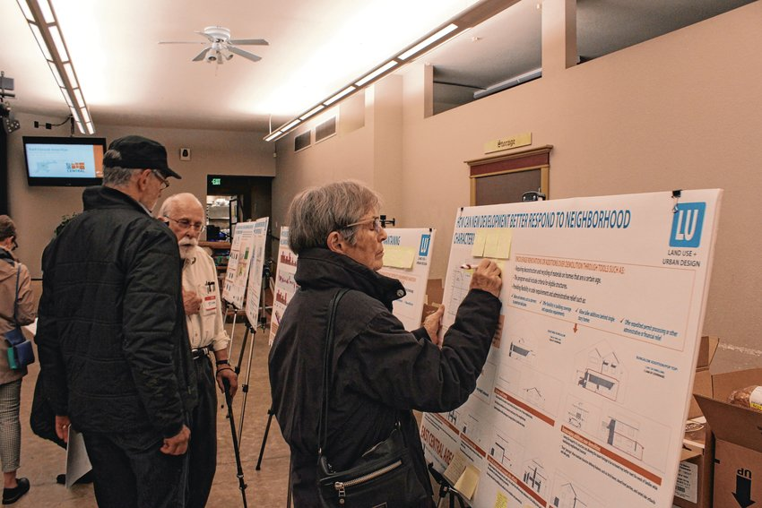 In this file photo from the summer, Sally Barton writes a comment on a board during the public comment event for the East Central Area Plan. The city is working on creating plans for all its neighborhoods.